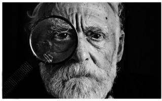 greyscale photo of man with magnifying glass